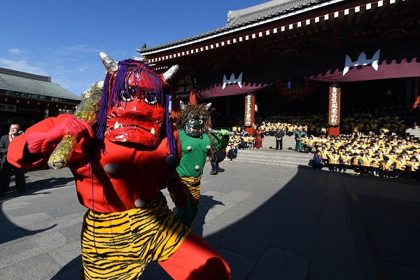 Two parents of kindergarten students, wearing demon-like masks to scare pupils, take part in a bean-throwing ceremony to drive away evils and bring good luck at the annual Setsubun Festival at the Sensoji Temple in Tokyo on February 3, 2016. Some 350 children attended the event to greet the coming of spring.        AFP PHOTO / TOSHIFUMI KITAMURA